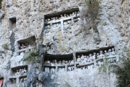 Tumba excavada en la roca con representaciones en madera de los hombres allí enterrados